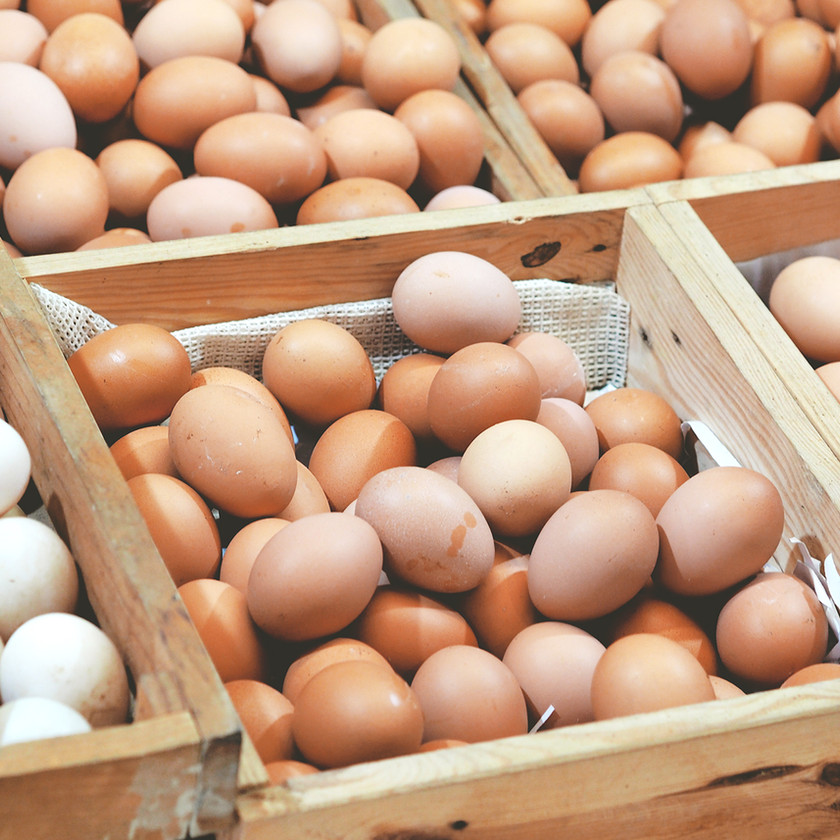 Brown and white eggs piled in wooden crates.