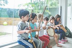 Crinças com instrumentos musicais de capoeira.