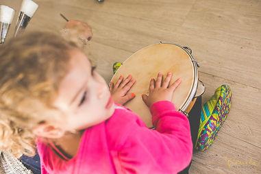 Criança com seu pandero em oficina e música.