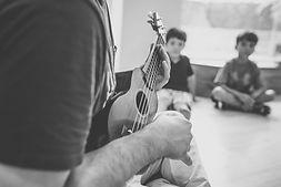 Professor tocando kulele em aula de música.