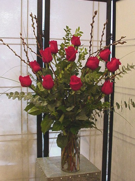 One dozen long stem roses in vase