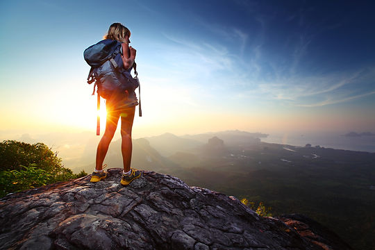 Young lady hiker standing with backpack on top of a mountain and enjoying sunrise.jpg