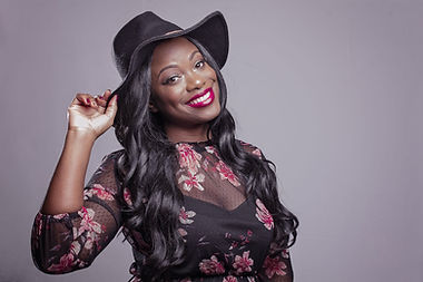 smiling-woman-holding-black-hat-713525.j