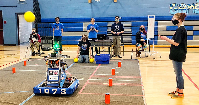 Students gathered driving a robot on carpet inside of a mini gym at Hollis Brookline Middle School.