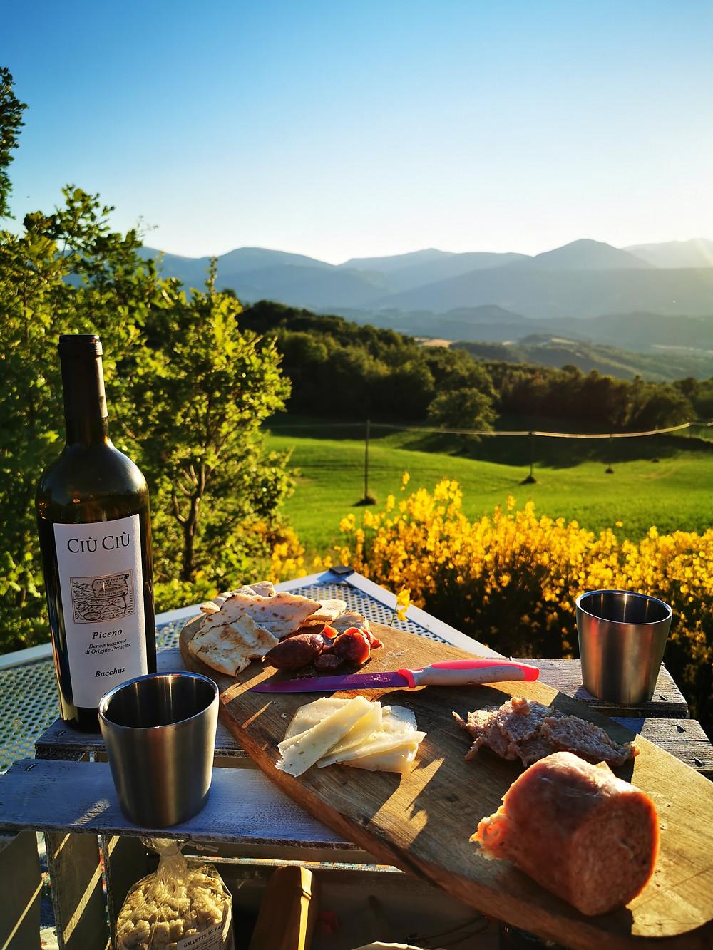 Aperitivo con prodotti tipici Umbri sopra al rooftop di CampUp. Bottiglia di vino della cantina Ciù Ciù, salame ciauscolo e pecorino.