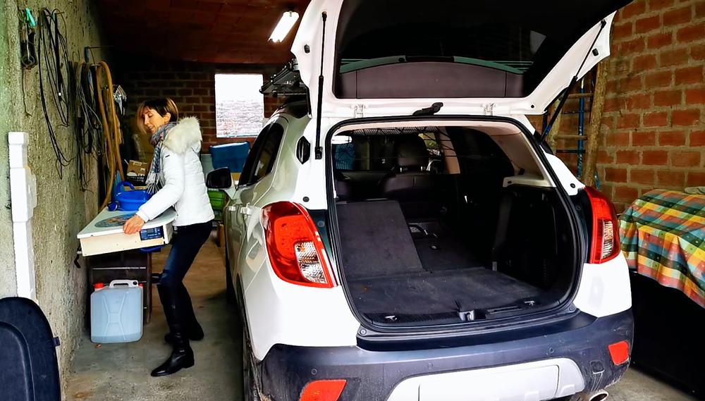 ragazza che tiene in mano la cucina rimovibile e baule auto aperto. La cucina nel baule auto si mette e toglie all'occorrenza.