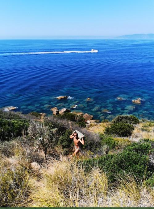 ragazzo che percorre un sentiero a picco sul mare a punta di torre ciana, monte argentario, Toscana