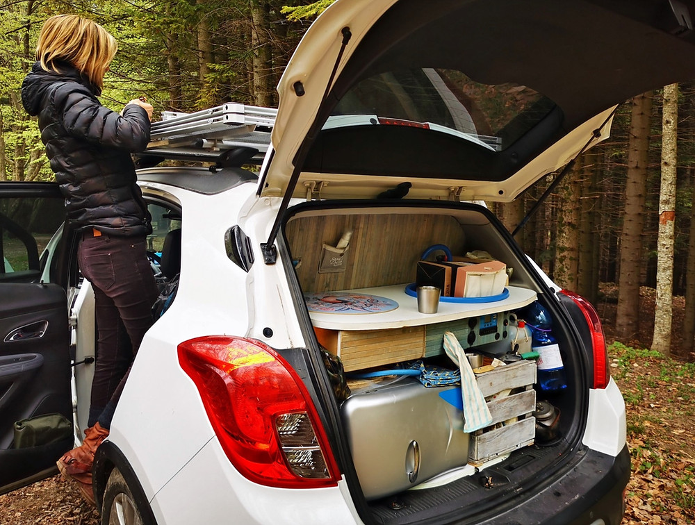 ragazza che apre il piano tenda da tetto auto e cucina nel baule in vista.