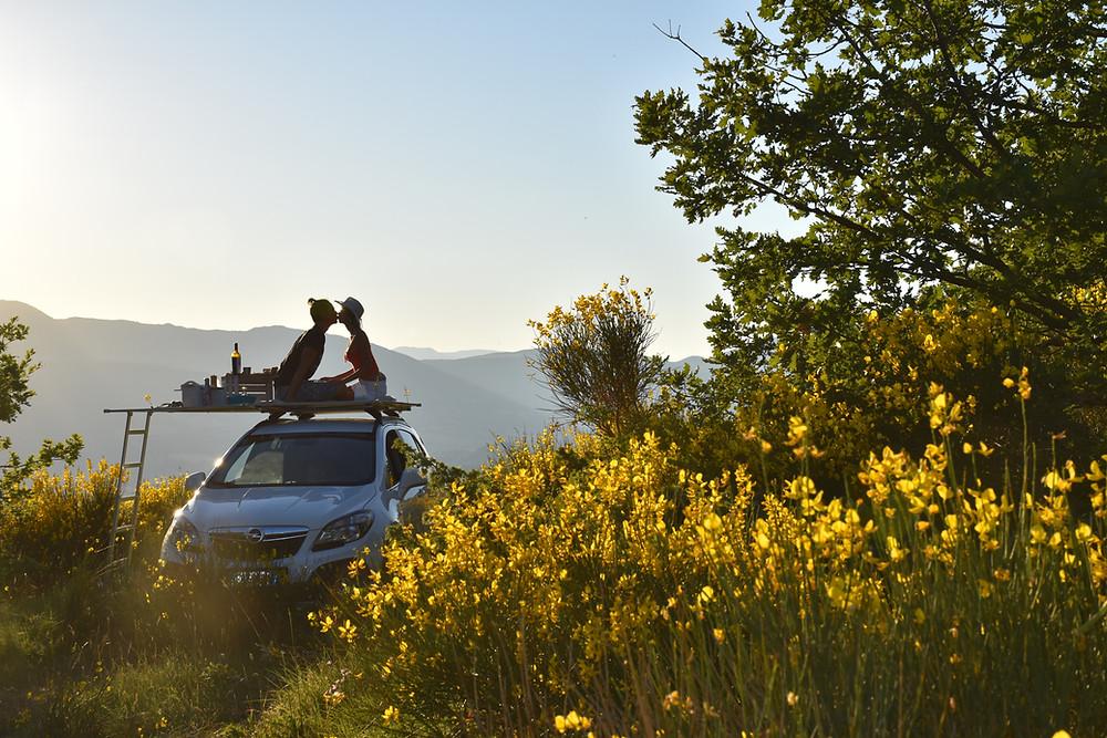 Rooftop di CampUp (macchina camperizzatata) allestito per un aperitivo al tramonto e contornato di ginestre gialle.