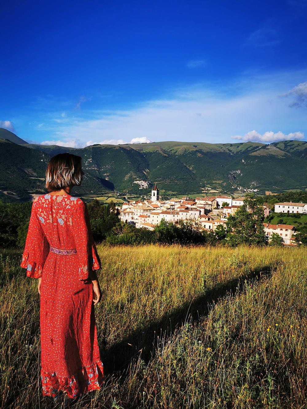 donna con un vestito rosso che guada dall'alto il paesino di Todiano