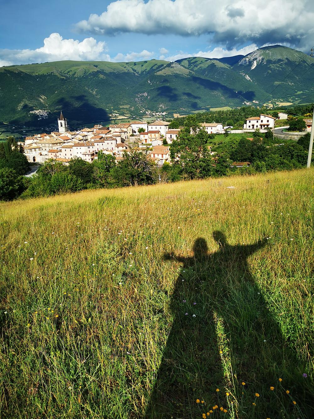 Le nostre ombre riflesse sull'erba e il paesino di Todiano
