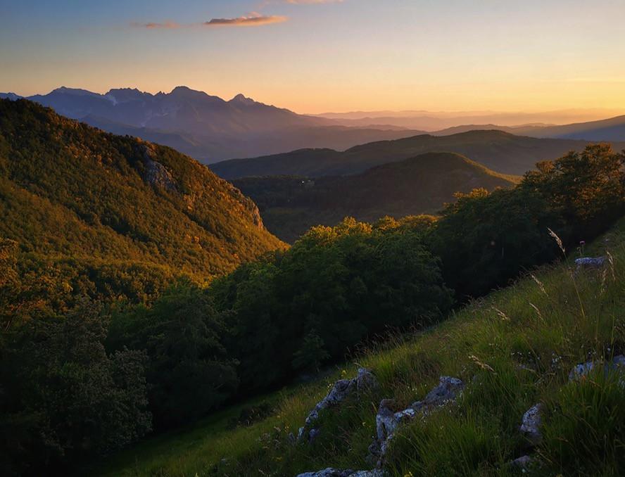 tramonto sulle alpi Apuane. in primo piano colline verdi e in lontananza montagne colorate di arancione, rosa e giallo dal tramonto