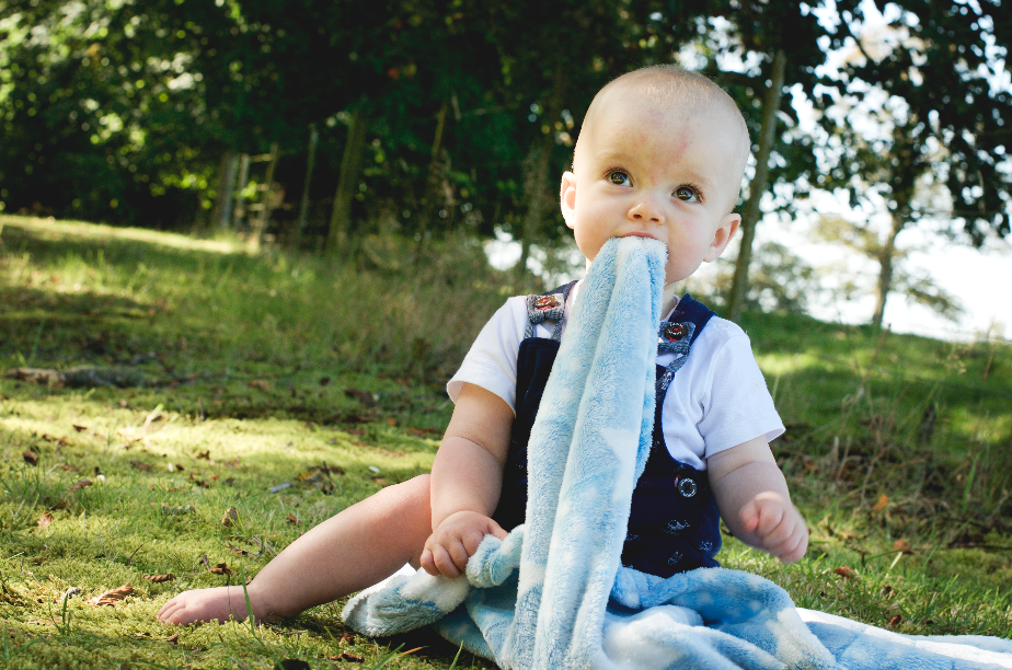 baby with blanket in mouth