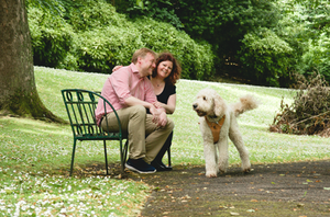 dog with owners on park bench