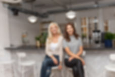 two women sitting on high stools smiling warmly
