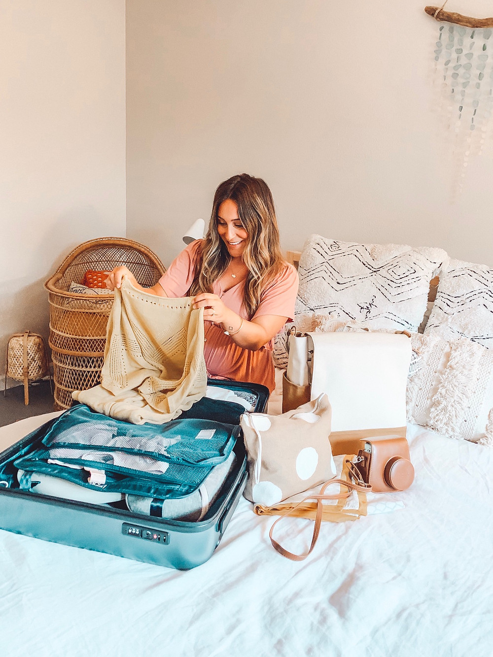 pregnant woman packing a blanket into a suitcase on a bed