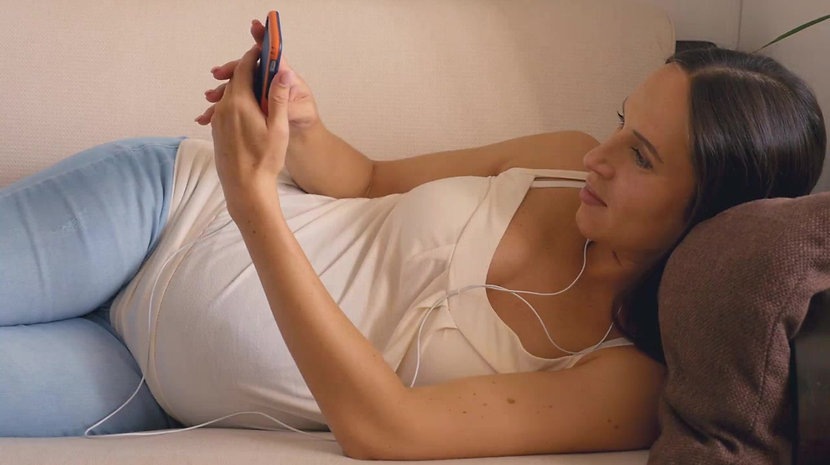 happy pregnant woman lying back listening to audio using earphones while looking at her phone