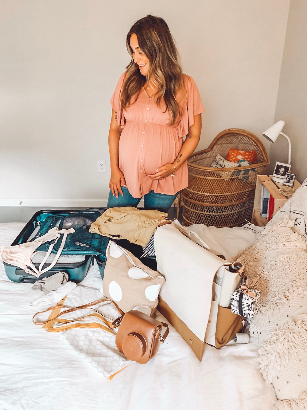 pregnant woman packing a suitcase and other bags on a bed