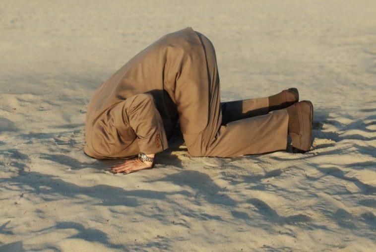 homem enterrando a cabeça na areia como uma avestruz