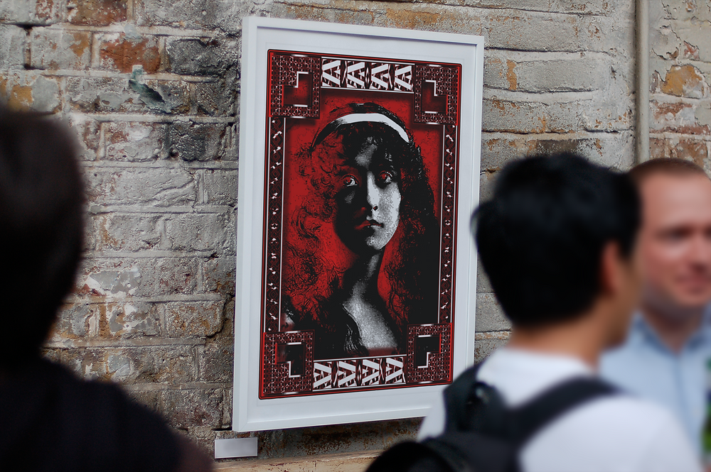 A red white and black fantasy portrait hanging in a frame.