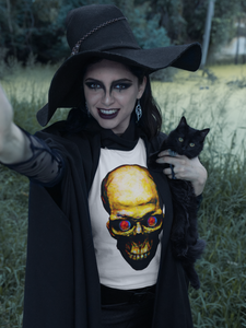 A goth style witch holding a black cat and wearing one of my skull t shirt designs.