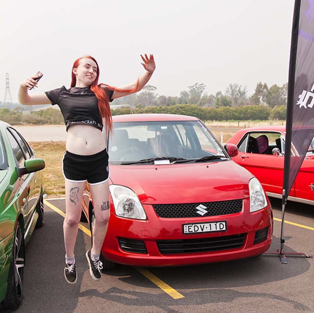 Jillian Helm jumping for joy at her first car display event with her Suzuki Swift