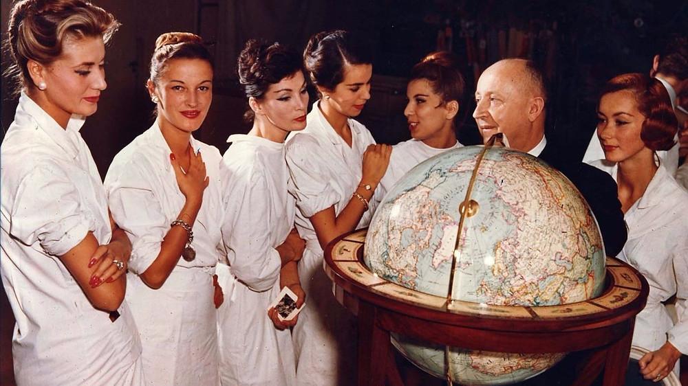 fashion designer Christian Dior flanked by models