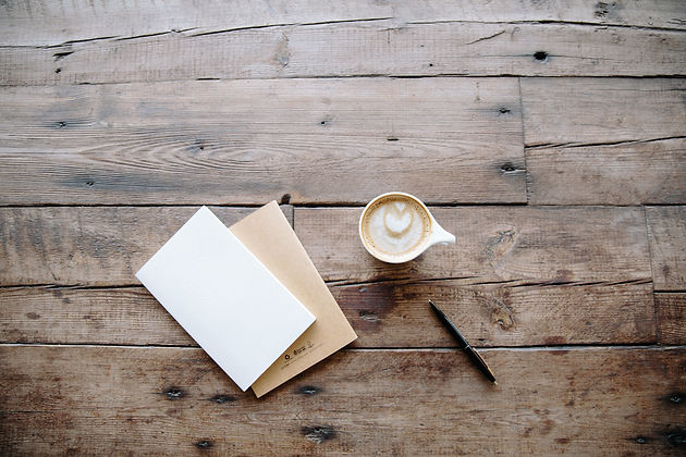 Notebook, coffee and pen on table