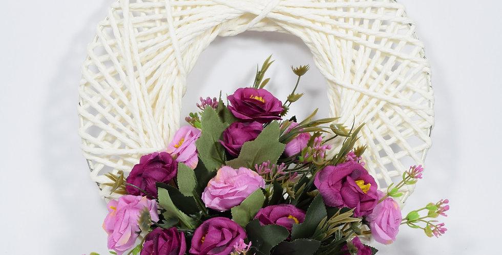 Στεφάνι με τεχνητές νεραγκούλες και τριαντάφυλλα, σε πλεκτή λευκή βάση.