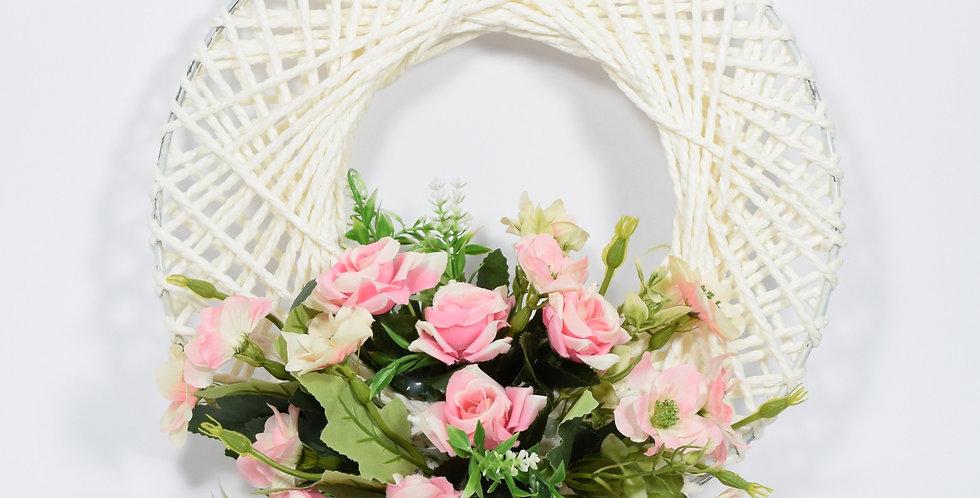 Στεφάνι με τεχνητά τριαντάφυλλα, σε πλεκτή λευκή βάση.