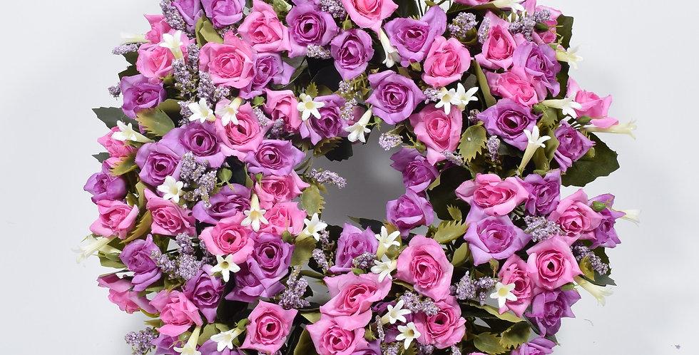 Στεφάνι με τεχνητά λουλούδιατριαντάφυλλα ροζ και λιλά, σε βάση από φελιζόλ.