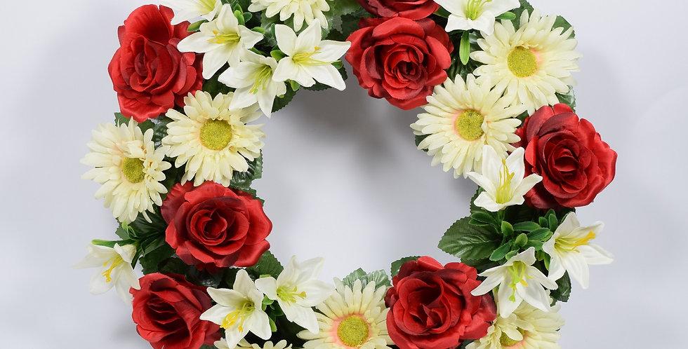 Στεφάνι με τεχνητές ζέρμπερες και κόκκινα τριαντάφυλλα, σε βάση από φελιζόλ.