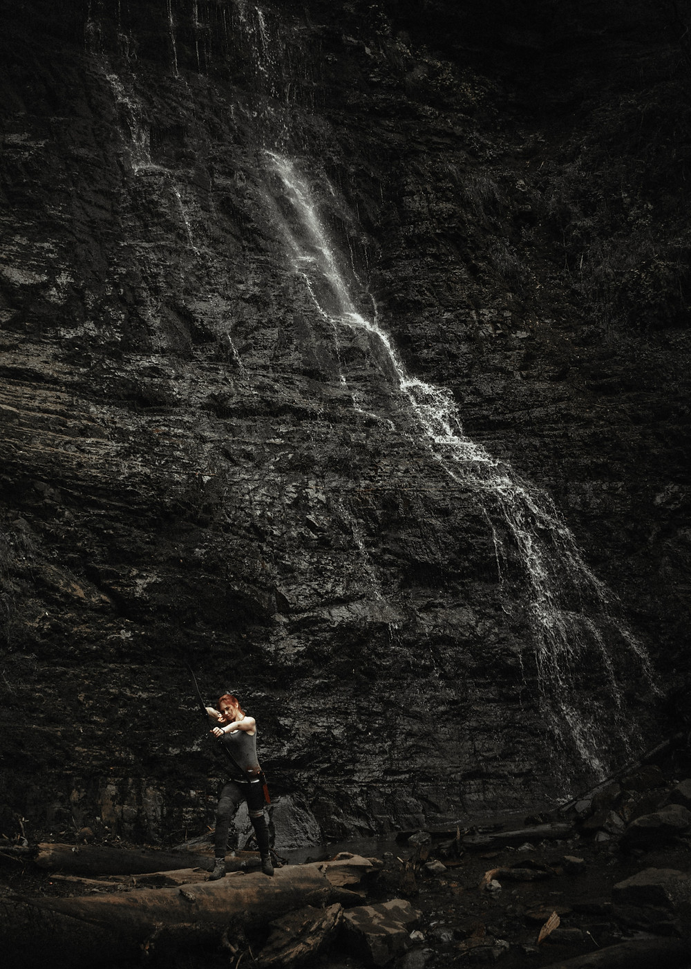 Lara Croft at the bottom of a bad ass rock formation and waterfall