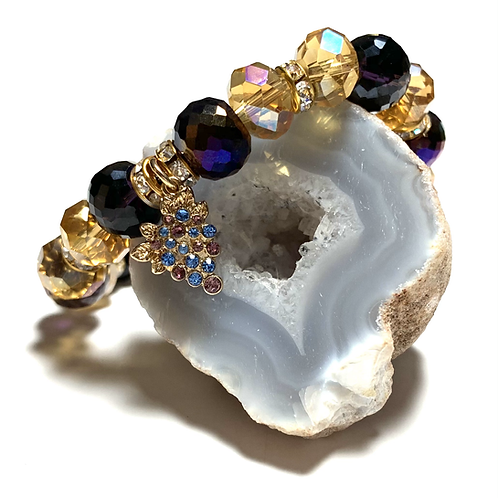 Gold toned with purple and black beads with a grape vine crystal charm