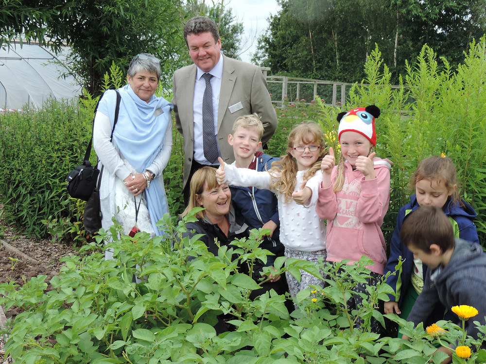 Judges Nicola Clarke and Joe Hayden meet pupils of Lord Scudamore Primary School in the schools garden.