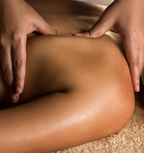 Closeup of the hands of a massage therapist rubbing out muscle knot on a patient's back