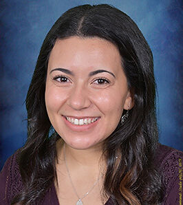 Professional headshot portrait of daycare administrator smiling with a blue background.