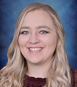 Professional headshot portrait of well-trained daycare teacher smiling with a blue background.