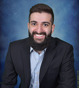 Professional headshot portrait of Daycare Co-Owner smiling with a blue background.