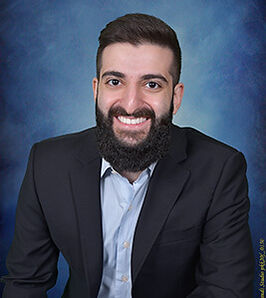 Professional headshot portrait of Preschool Owner smiling with a blue background.