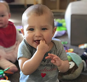 Happy baby at daycare with fingers in his mouth in the infant classroom