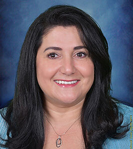 Professional headshot portrait of Preschool Director smiling with a blue background.