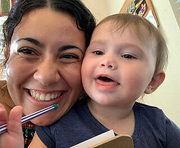 Preschool Teacher taking a selfie with a smiling 1 year old who is holding a pencil.