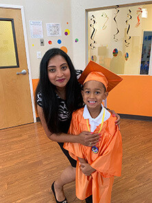 Child wearing cap and gown graduating Pre-Kindergarten
