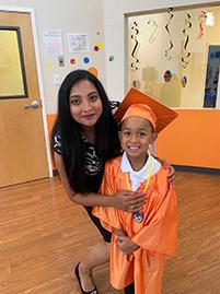 Child wearing cap and gown graduating Pre-Kindergarten