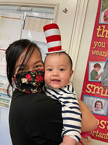 Mom holding her infant on Dr. Seuss day