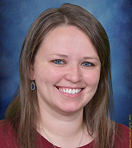 Professional headshot portrait of Preschool administrator smiling with a blue background.