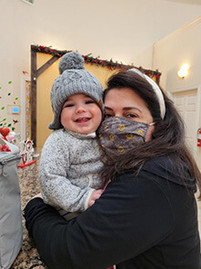 Preschool director holding baby in school lobby