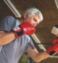Older man boxing in gym. Senior man with
