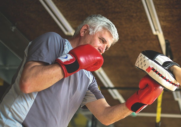 Older man boxing in gym. Senior man with